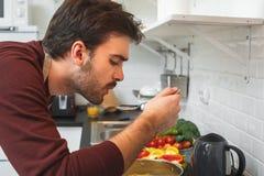 Hombre joven que cocina la cena romántica en casa que enfría hacia fuera la sopa fotografía de archivo libre de regalías