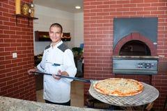 Hombre joven que cocina la pizza Foto de archivo libre de regalías