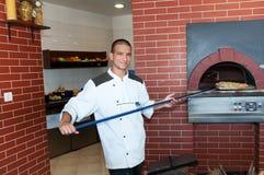 Hombre joven que cocina la pizza Imágenes de archivo libres de regalías