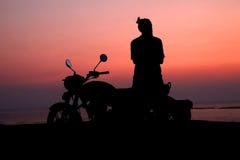 Hombre joven que coloca la moto cercana y que disfruta de la opinión de la puesta del sol Foto de archivo libre de regalías