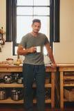 Hombre joven que come café de restauración en mañana Fotografía de archivo