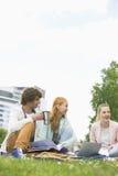 Hombre joven que come café mientras que estudia con los amigos femeninos en el campus de la universidad Imagen de archivo