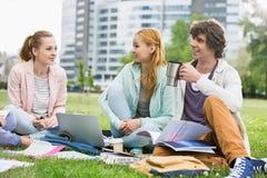 Hombre joven que come café mientras que estudia con los amigos femeninos en el campus de la universidad Imagenes de archivo