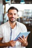 Hombre joven que come la taza de café usando la tableta Imágenes de archivo libres de regalías