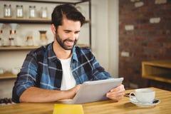 Hombre joven que come la taza de café usando la tableta Fotos de archivo libres de regalías