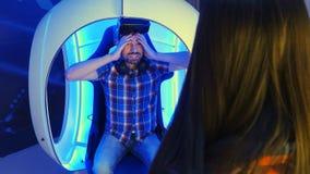 Hombre joven que comparte sus emociones con la novia después de experiencia de la realidad virtual Imagen de archivo libre de regalías