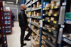 Hombre joven que compra una herramienta de mano en tienda del hardware fotos de archivo libres de regalías