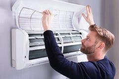 Hombre joven que comprueba el acondicionador de aire fotos de archivo libres de regalías