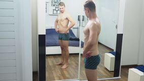 Hombre joven que comprueba sus músculos delante de un espejo en el dormitorio almacen de metraje de vídeo