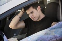 Hombre joven que conduce el coche, sosteniendo un mapa confundido Foto de archivo libre de regalías