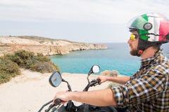 Hombre joven que conduce la bici de alquiler del patio en el camino de la playa en la isla de los Milos hacia la playa de Firipla Foto de archivo libre de regalías