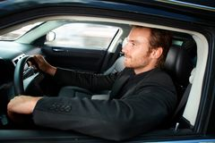 Hombre joven que conduce la sonrisa de lujo del coche Imágenes de archivo libres de regalías