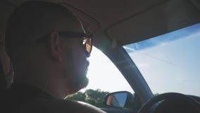 Hombre joven que conduce un coche Hombre que se sienta y que conduce en el coche Viaje de un tiempo adentro soleado almacen de metraje de vídeo