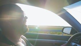 Hombre joven que conduce un coche Hombre que se sienta y que conduce en el coche Viaje de un tiempo adentro soleado almacen de video
