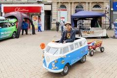 Hombre joven que conduce una autocaravana miniatura de Volkswagen fotos de archivo