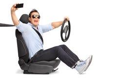 Hombre joven que conduce y que toma un selfie Imagenes de archivo