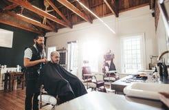 Hombre joven que consigue corte de pelo en la peluquería de caballeros fotografía de archivo libre de regalías