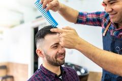 Hombre joven que consigue un peinado en una barbería imágenes de archivo libres de regalías