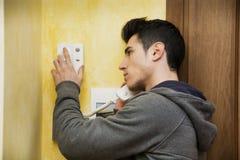 Hombre joven que contesta al intercomunicador en un apartamento Imagen de archivo