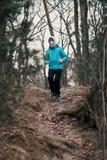 Hombre joven que corre al aire libre durante entrenamiento en un bosque entre la hoja Foto de archivo libre de regalías