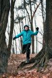 Hombre joven que corre al aire libre durante entrenamiento en un bosque entre la hoja Imagen de archivo libre de regalías