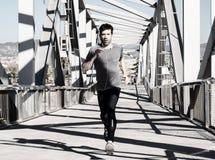 Hombre joven que corre con los auriculares Fotografía de archivo