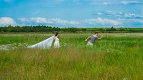 Hombre joven que corre de su muchacha en el campo Imagen de archivo
