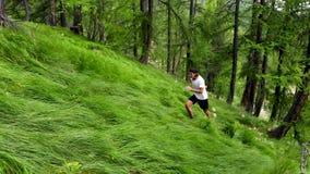 Hombre joven que corre en el bosque filmado por el vídeo 4K del abejón almacen de metraje de vídeo