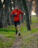 Hombre joven que corre en el rastro en el bosque salvaje Imagen de archivo libre de regalías