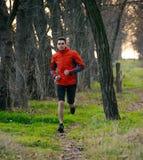 Hombre joven que corre en el rastro en el bosque salvaje Fotos de archivo