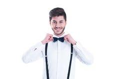 Hombre joven que corrige su corbata de lazo, sonriendo Aislado en el CCB blanco Fotografía de archivo