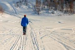 Hombre joven que cruza el río en el hielo en invierno Foto de archivo