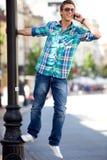 Hombre joven que cuelga en el poste de la lámpara Imagen de archivo libre de regalías