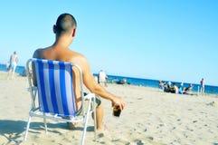 Hombre joven que cuelga hacia fuera en la playa, con un vidrio con la bebida de la cola Imagen de archivo