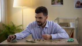 Hombre joven que cuenta el dinero y que mira el coche del juguete, ahorros para la compra, sueño almacen de metraje de vídeo