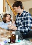 Hombre joven que cuida para la muchacha enferma Foto de archivo libre de regalías