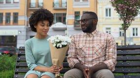Hombre joven que da el ramo de la flor blanca al banco que se sienta de la mujer, primera fecha torpe almacen de metraje de vídeo