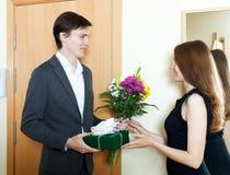Hombre joven que da las flores y el regalo imagen de archivo libre de regalías