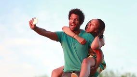 Hombre joven que da a su novia un paseo del transporte por ferrocarril mientras que toma el selfie metrajes