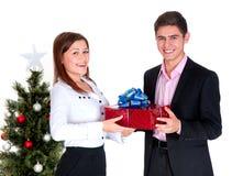 Hombre joven que da a un regalo una muchacha Imagen de archivo