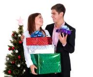 Hombre joven que da a un regalo una muchacha en la Navidad Fotos de archivo libres de regalías