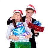 Hombre joven que da a un regalo una muchacha en la Navidad Imagen de archivo libre de regalías