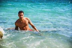 Hombre joven que defiende en agua la orilla del mar o del océano, imagen de archivo
