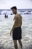 Hombre joven que defiende en la playa el océano imagen de archivo libre de regalías