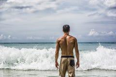 Hombre joven que defiende en la playa el océano imágenes de archivo libres de regalías