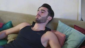 Hombre joven que descansa sobre el sofá Imagen de archivo