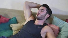 Hombre joven que descansa sobre el sofá Fotografía de archivo libre de regalías