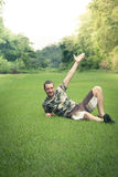 Hombre joven que descansa sobre la hierba con el brazo extendido al cielo Imágenes de archivo libres de regalías