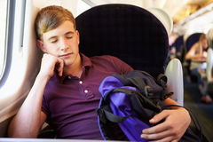 Hombre joven que descansa sobre viaje de tren Imagen de archivo libre de regalías