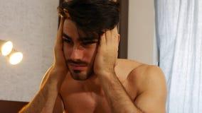 Hombre joven que despierta con dolor de cabeza Imagen de archivo libre de regalías